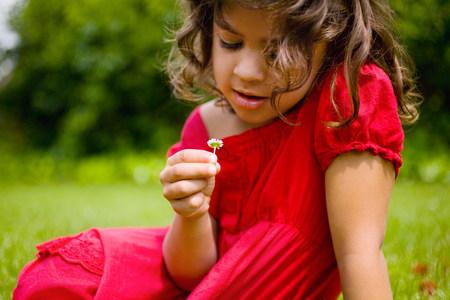 A girl holding a daisy Stock Photo