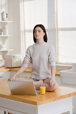 Meditating woman with laptop Stock Photo
