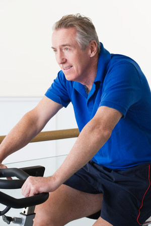 Mature man cycling on an exercise bike