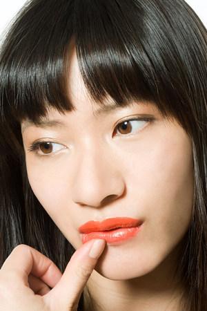 Rührende Lippe der jungen Frau mit dem Daumen Standard-Bild - 85900103