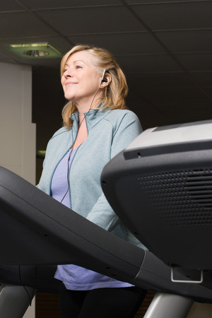 A mature woman listening to music whilst exercising Stock Photo