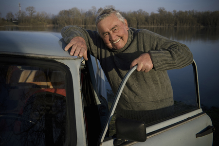 Senior man standing by car on riverside, smiling, portrait
