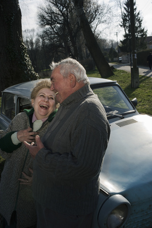 Senior couple leaning on car in countryside, laughing