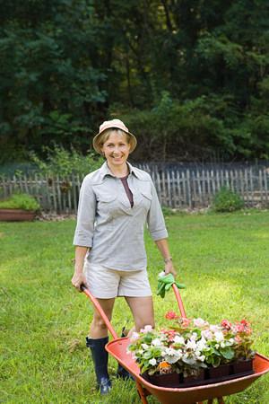 Woman with wheelbarrow of plants Stock Photo