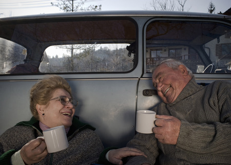 Senior couple sitting by car in countryside, holding cups, smiling Stock Photo