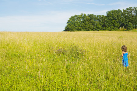 A girl standing in a field of long grass Stock Photo