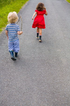 Boy and girl running down a road