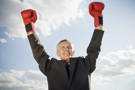 Businessman wearing boxing gloves.