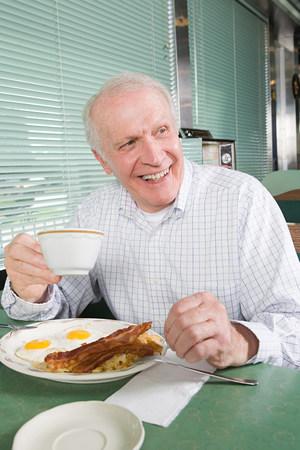 年配の男性が揚げられていた朝食を食べる 写真素材