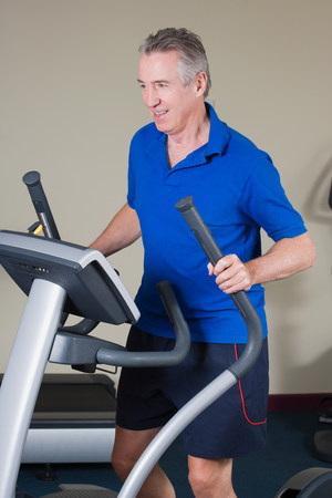 Mature man exercising on a cross trainer Stock Photo