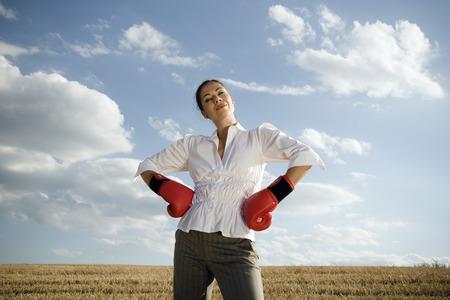 Businesswoman in wheat field wearing boxing gloves.