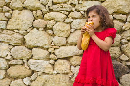 A girl eating a baguette Stock Photo
