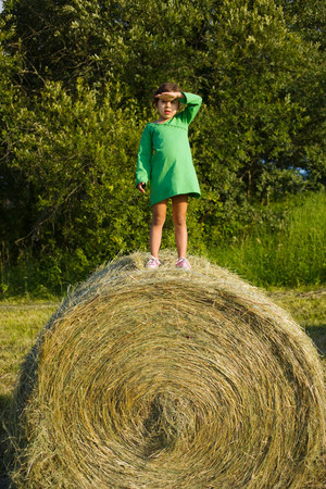 A girl standing on a haystack