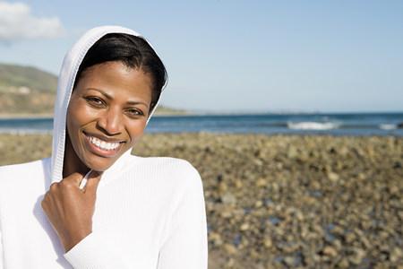 A smiling woman on a shingle beach Stock fotó