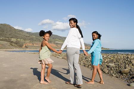 Una madre e hijas cogidos de la mano. Foto de archivo