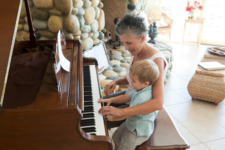 Grandmother and grandson playing the piano