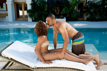 Couple kissing on sun lounger by pool Stock Photo