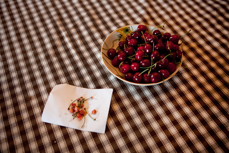 Bowl of cherries on checked tablecloth