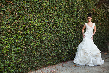Young woman wearing wedding dress, standing by hedge
