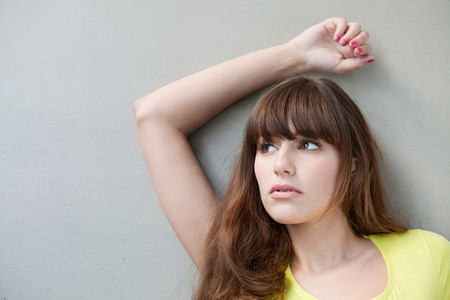 Portrait of a young woman with arm raised Stock Photo