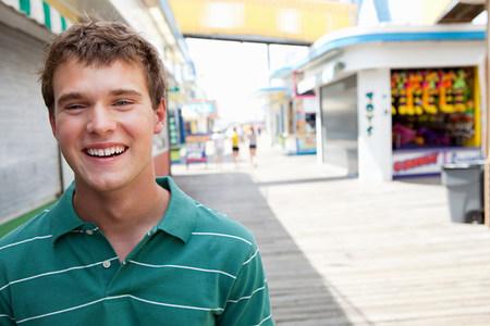 Happy teenage boy on boardwalk