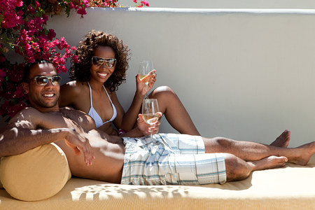 Happy couple on lounger with wine Imagens