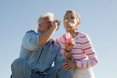 Mature couple blowing bubbles