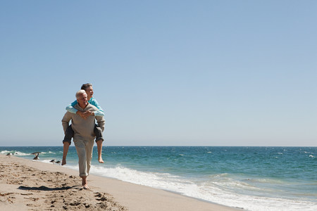Mature couple piggybacking on beach