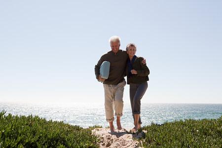 Mature couple walking over dune Banque d'images