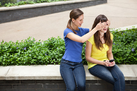 Girl covering friends eyes
