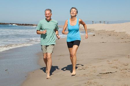 Senior couple jogging on beach