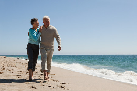 Mature couple walking on the beach Stock Photo