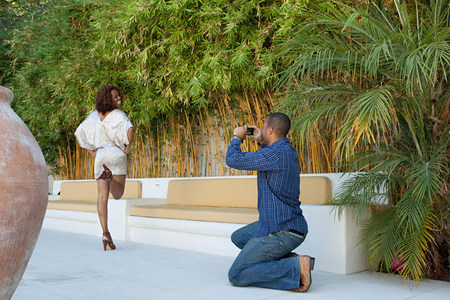 Man taking a picture of girlfriend as she poses for camera