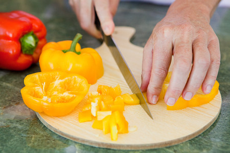 Woman chopping peppers on chopping board
