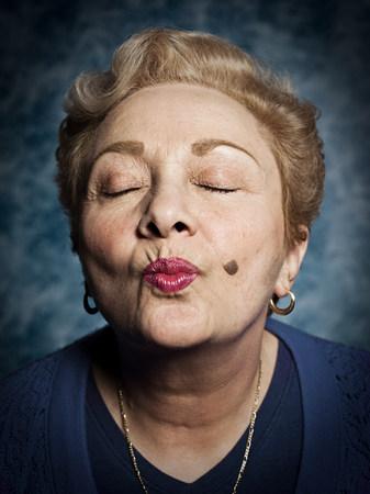 Senior woman blowing kiss, eyes closed