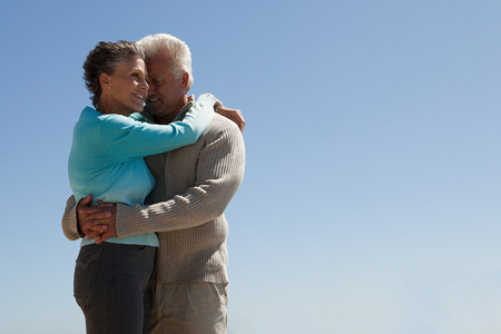 Mature couple hugging against blue sky Stock Photo