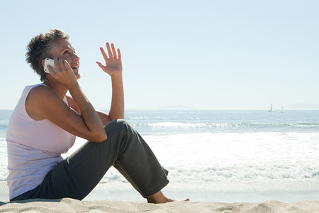 Senior woman using cell phone on beach Imagens