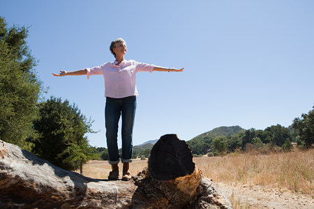 Senior woman standing on a log with open arms