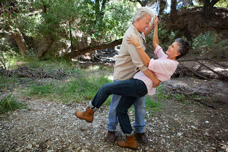 Mature couple dancing in forest 스톡 콘텐츠