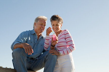 60 64 years: Mature couple with bubbles Stock Photo