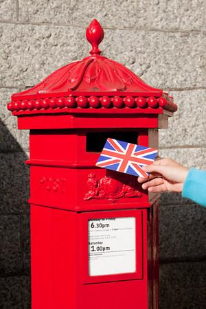 ロンドン郵便ポストにはがきを置く人