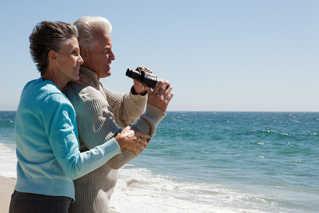 Mature couple at the beach with binoculars Stock Photo