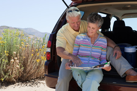 Mature couple sitting on boot of car with map Stock Photo