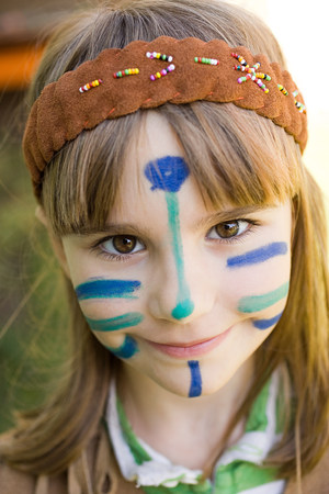Girl dressed in Native American costume with face painted
