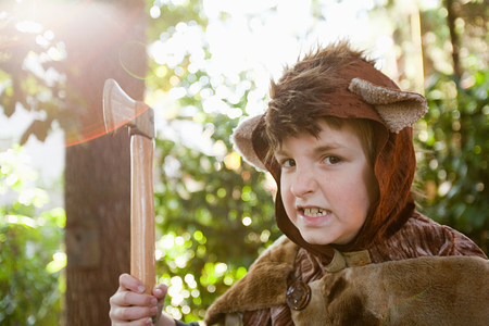 Boy dressed up as bear with toy axe Stock Photo