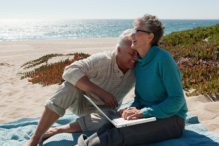 Mature couple using laptop at the beach