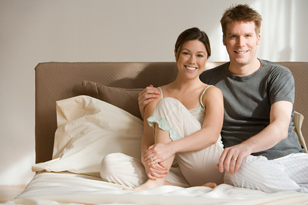 Couple sitting on their bed