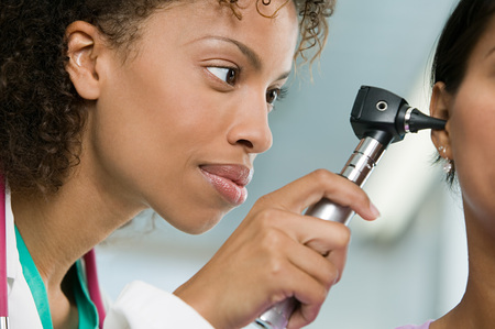 Doctor examining patient with otoscope