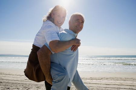 Hogere man dragende vrouw op rug Stockfoto