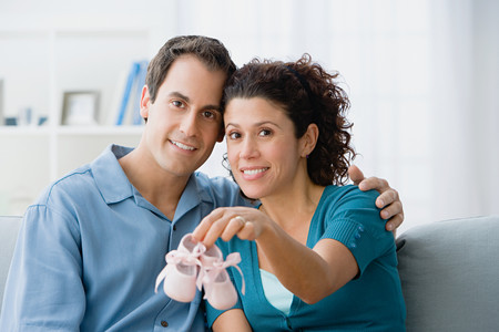 Couple holding a pair of baby booties